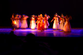 Dancers are dancing against black background. Photograph is taken with long expose, motion blur.