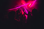 People dancing in a nightclub with smoke machines and strobe lighting around them.