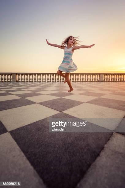 Baile de chica joven en el paseo marítimo en la Toscana de Livorno