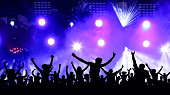 Dancing youth party, illustration. Crowd of cheerful people at a concert. Silhouettes of a crowd of fans in front of bright scene lights