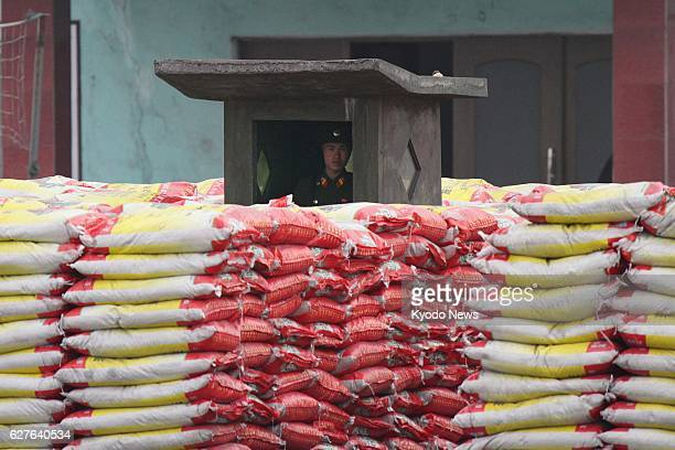Dandong China A North Korean soldier seen from the Chinese city of Dandong keeps watch on a pile of bags trucked from China apparently containing...