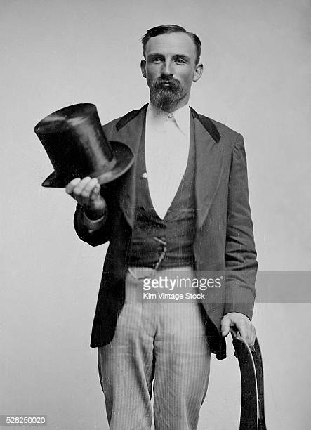 A dandy stylish man strikes a pose while holding his beaver skin top hat
