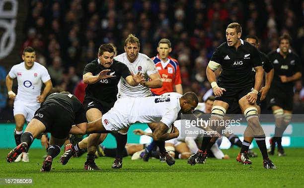 Dane Coles of New Zealand tackles David Paice of England during the QBE International match between England and New Zealand at Twickenham Stadium on...