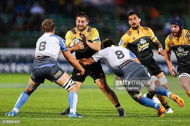 Dane Coles of the Hurricanes is tackled by Angus Cottrell and Ben McCalman of the Force during the round four Super Rugby match between the...
