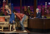 Dane Cook lays a kiss on the backside of actress Charlize Theron on the set of the 'Tonight Show With Jay Leno' as Leno looks on October 4 2005 at...