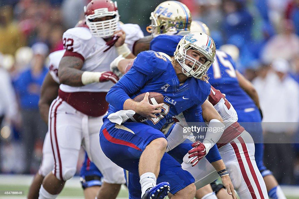 Dane Evans of the Tulsa Golden Hurricanes is sacked by Caleb Gastelum of the Oklahoma Sooners at HA Chapman Stadium on September 6 2014 in Tulsa...