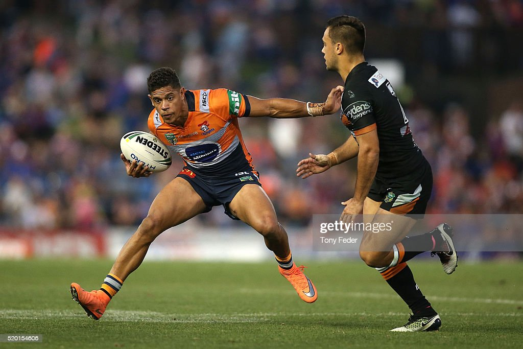 Dane Gagai of the Knights avoids a tackle by Luke Brooks of the Tigers during the round six NRL match between the Newcastle Knights and the Wests Tigers at Hunter Stadium on April 10, 2016 in Newcastle, Australia.
