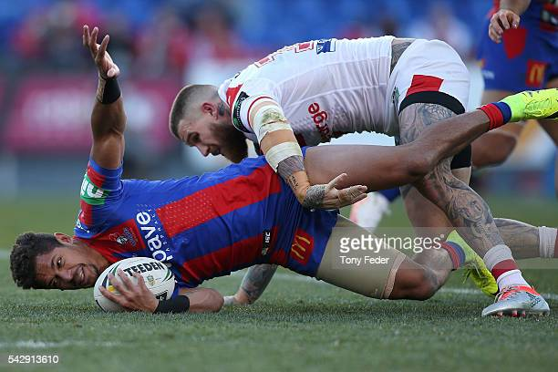 Dane Gagai of the Knights is tackled by Josh Dugan of the Dragons during the round 16 NRL match between the Newcastle Knights and the St George...