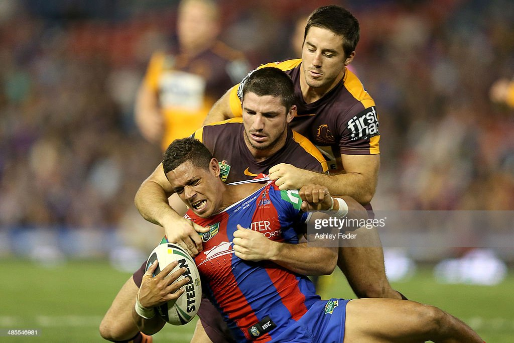 Dane Gagai of the Knights is tackled by Josh McGuire and <a gi-track='captionPersonalityLinkClicked' href=/galleries/search?phrase=Ben+Hunt+-+Rugby+Player&family=editorial&specificpeople=13397153 ng-click='$event.stopPropagation()'>Ben Hunt</a> of the Broncos during the round seven NRL match between the Newcastle Knights and the Brisbane Broncos at Hunter Stadium on April 18, 2014 in Newcastle, Australia.