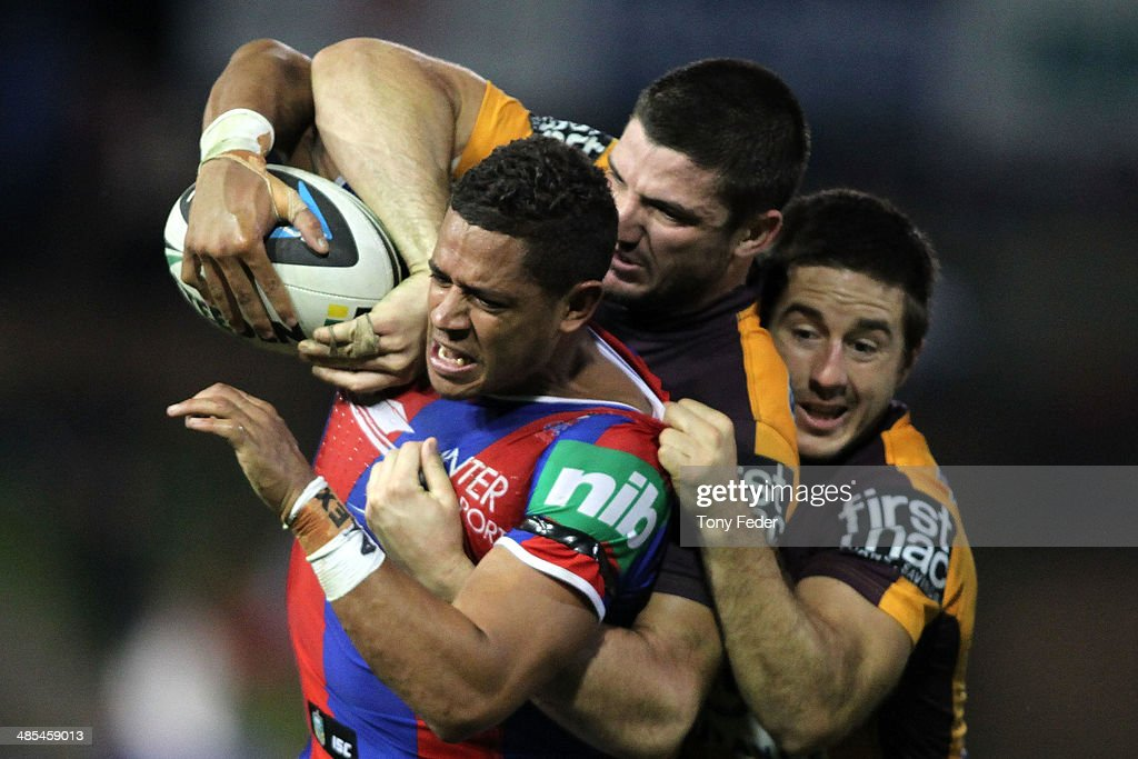 Dane Gagai of the Knights is tackled by the Broncos defence during the round seven NRL match between the Newcastle Knights and the Brisbane Broncos at Hunter Stadium on April 18, 2014 in Newcastle, Australia.