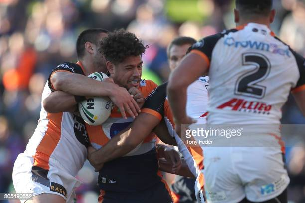 Dane Gagai of the Knights is tackled by the Tigers defence during the round 17 NRL match between the Newcastle Knights and the Wests TIgers at...