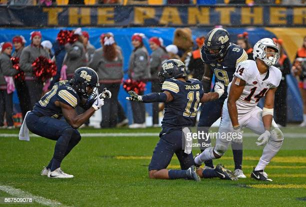 Dane Jackson of the Pittsburgh Panthers reacts with teammates after breaking up a pass intended for Andre Levrone of the Virginia Cavaliers in the...