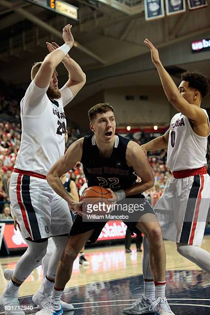 Dane Pineau of the Saint Mary's Gaels controls the ball against Przemek Karnowski and Silas Melson of the Gonzaga Bulldogs in the second half at...