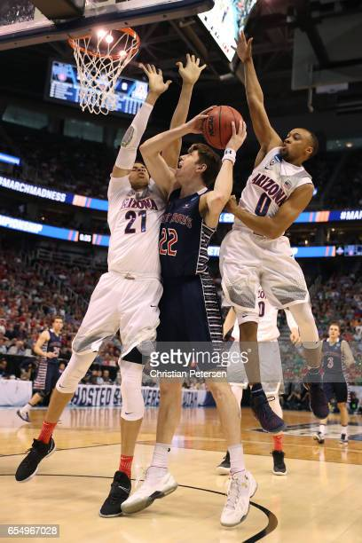 Dane Pineau of the St Mary's Gaels is defended by Chance Comanche and Parker JacksonCartwright of the Arizona Wildcats during the second round of the...
