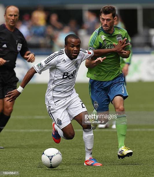Dane Richards of the Vancouver Whitecaps dribbles against Brad Evans of the Seattle Sounders FC at CenturyLink Field on August 18 2012 in Seattle...