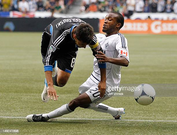 Dane Richards of the Vancouver Whitecaps FC and Chris Wondolowski of the San Jose Earthquakes collide as they battle for the ball during their MLS...