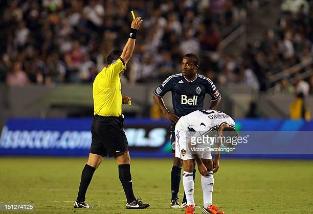 Dane Richards of the Vancouver Whitecaps looks at referee Baldomero Toledo as Toledo books Richards with a yellow card during the MLS match at The...