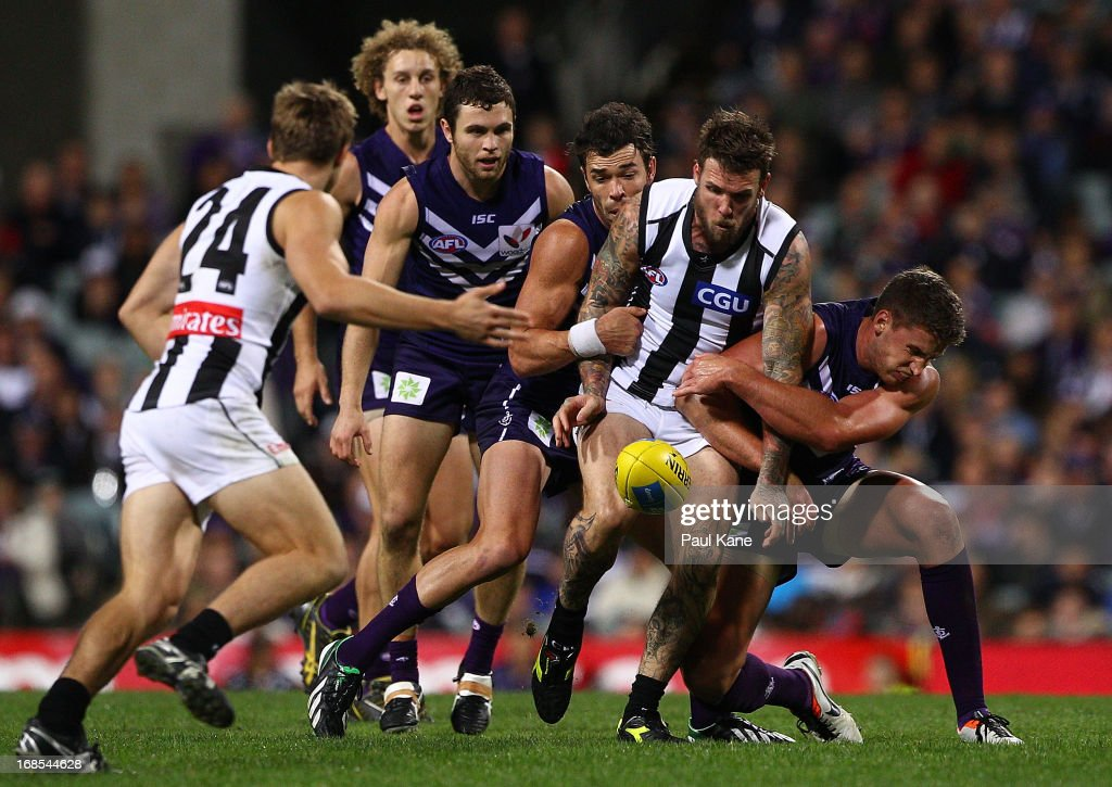 <a gi-track='captionPersonalityLinkClicked' href=/galleries/search?phrase=Dane+Swan&family=editorial&specificpeople=596987 ng-click='$event.stopPropagation()'>Dane Swan</a> of the Magpies gets his kick away while being tackled by Ryan Crowley and Jack Hannath of the Dockers during the round seven AFL match between the Fremantle Dockers and the Collingwood Magpies at Patersons Stadium on May 11, 2013 in Perth, Australia.
