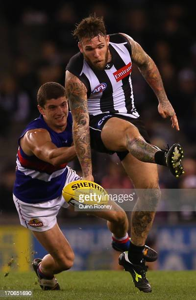 Dane Swan of the Magpies kicks whilst being tackled by Tom Liberatore of the Bulldogs during the round twelve AFL match between the Collingwood...