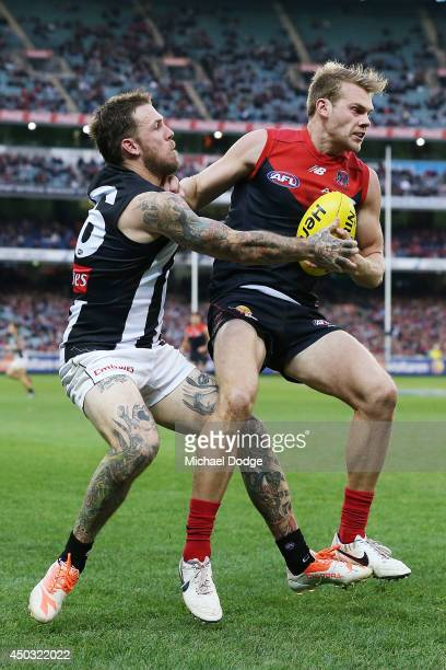 Dane Swan of the Magpies tackles Jack Watts of the Demons during the round 12 AFL match between the Melbourne Demons and the Collingwood Magpies at...