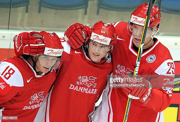 Danes Mads Chistensen and Morten Madsen congratulate Julian Jakobsen of Minnesota Wild after his scoring during their preliminary round group D game...