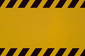 Yellow wall striped with black that can be used as background for making a composition about topics such as construction, danger or hazardous product.
