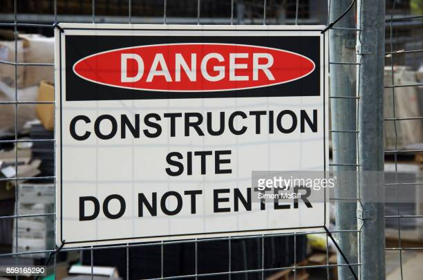 'Danger - Construction Site - Do Not Enter' site on the wire fence of a construction site for a residential apartment block
