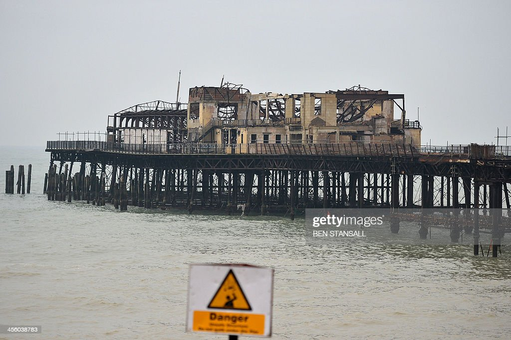 A 'danger' sign stands in front of the burnt-out remains of Hastings Pier in Hastings, southern England, on December 13, 2013 ahead of the start of a multi-million pound regeneration project. Hastings Pier was originally constructed in opulent style in the late 19th century seeing its heyday in the 1930s and hosting music concerts by major artists including The Rolling Stones in the 1960s and 70s. After undergoing various additions and re-construction to repair storm and fire damage throughout the 20th century the Victorian pier finally suffered a devastating fire in 2010 which destroyed much of the superstructure leaving just a burnt out shell. Following a Heritage Lottery Fund (HLF) grant and money from other funds a 14 million GBP regeneration project is set to begin work on January 6, 2014. AFP PHOTO / BEN STANSALL