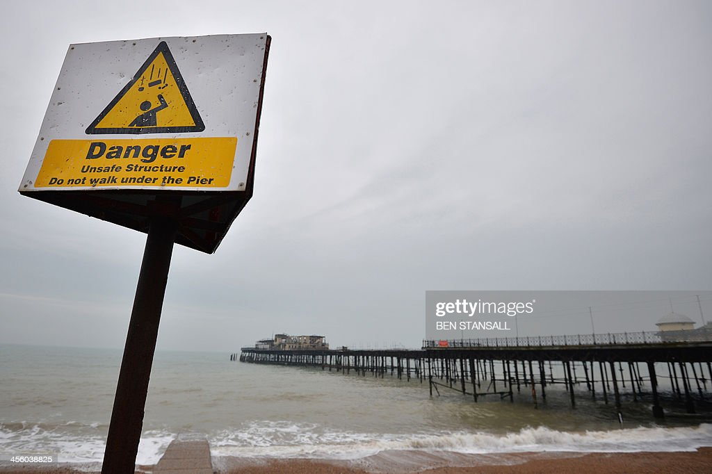 A 'danger' sign stands in front of the burnt-out remains of Hastings Pier in Hastings, southern England, on December 13, 2013 ahead of the start of a multi-million pound regeneration project. Hastings Pier was originally constructed in opulent style in the late 19th century seeing its heyday in the 1930s and hosting music concerts by major artists including The Rolling Stones in the 1960s and 70s. After undergoing various additions and re-construction to repair storm and fire damage throughout the 20th century the Victorian pier finally suffered a devastating fire in 2010 which destroyed much of the superstructure leaving just a burnt out shell. Following a Heritage Lottery Fund (HLF) grant and money from other funds a 14 million GBP regeneration project is set to begin work on January 6, 2014.