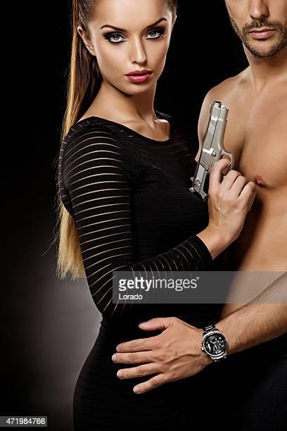 dangerous couple posing with gun