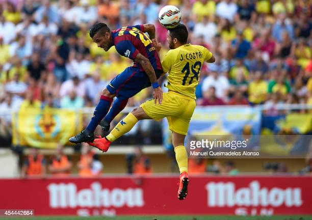 Dani Alves of Barcelona competes for a high ball with Jaume Costa of Villarreal during the La Liga match between Villarreal CF and FC Barcelona at El...