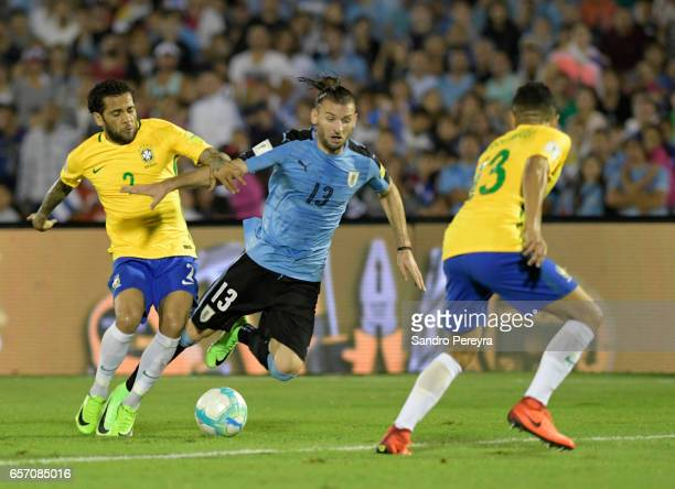 Dani Alves of Brasil competes for the ball with Gaston Silva and Marquinhos of Brazil fight for the ball during a match between Uruguay and Brazil as...