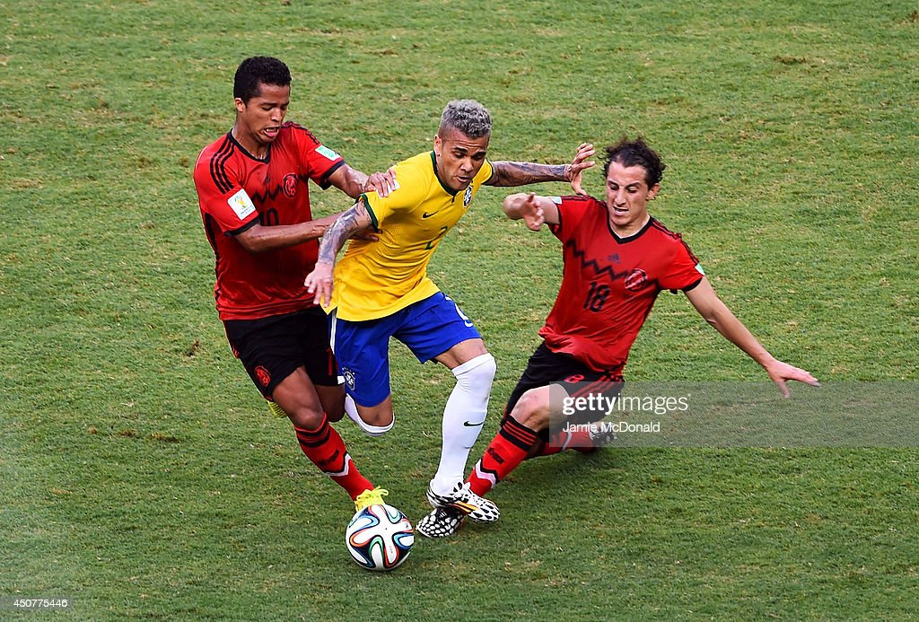 <a gi-track='captionPersonalityLinkClicked' href=/galleries/search?phrase=Dani+Alves&family=editorial&specificpeople=2191863 ng-click='$event.stopPropagation()'>Dani Alves</a> of Brazil is challenged by <a gi-track='captionPersonalityLinkClicked' href=/galleries/search?phrase=Giovani+dos+Santos&family=editorial&specificpeople=4435901 ng-click='$event.stopPropagation()'>Giovani dos Santos</a> (L) and <a gi-track='captionPersonalityLinkClicked' href=/galleries/search?phrase=Andres+Guardado&family=editorial&specificpeople=465479 ng-click='$event.stopPropagation()'>Andres Guardado</a> of Mexico during the 2014 FIFA World Cup Brazil Group A match between Brazil and Mexico at Castelao on June 17, 2014 in Fortaleza, Brazil.
