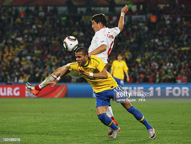 Dani Alves of Brazil vies for the ball with Carlos Carmona of Chile during the 2010 FIFA World Cup South Africa Round of Sixteen match between Brazil...