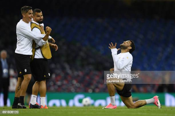 Dani Alves of Juventus celebrates as Paulo Dybala of Juventus and Tomas Rincon of Juventus look on during a Juventus/Real Madrid training session...
