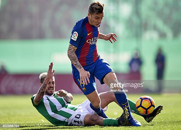 Dani Ceballos of Real Betis Balompie competes for the ball with Lucas Digne of FC Barcelona during the La Liga match between Real Betis Balompie and...