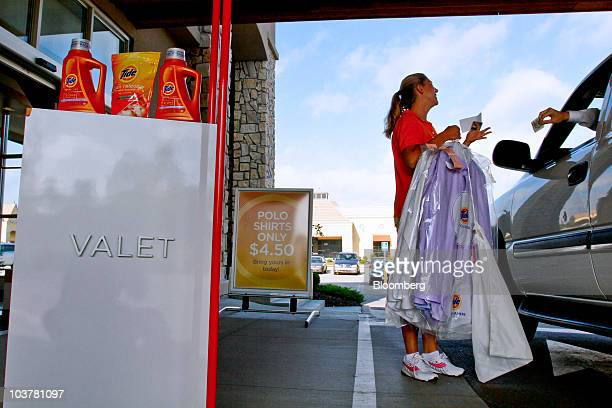 Dani McVay a customer service representative delivers a dry cleaning order to a customer's car in the valet service drivethru at the Procter Gamble...