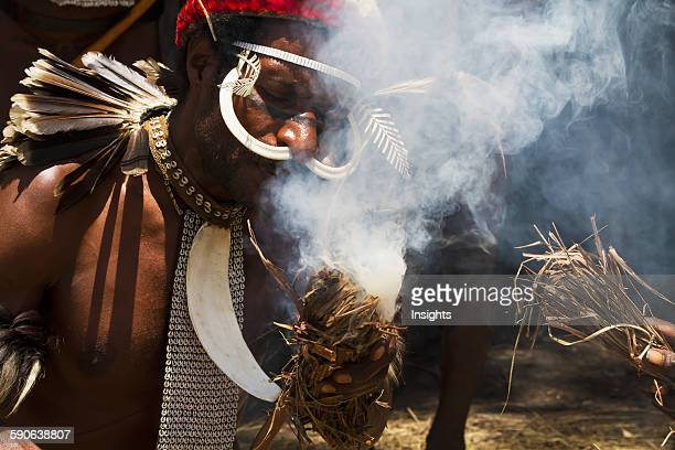 Dani men wearing an elaborate headdress of bird of paradise or cassowary feathers lighting a fire Obia Village Baliem Valley Central Highlands of...
