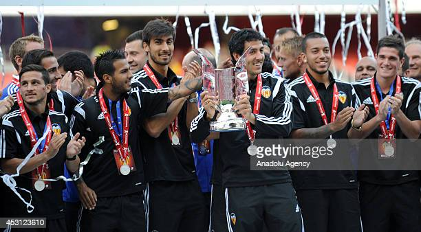 Dani Parejo of Valencia and Valencia players pose with the trophy after the Emirates Cup 2014 match between Arsenal and AS Monaco at Emirates Stadium...