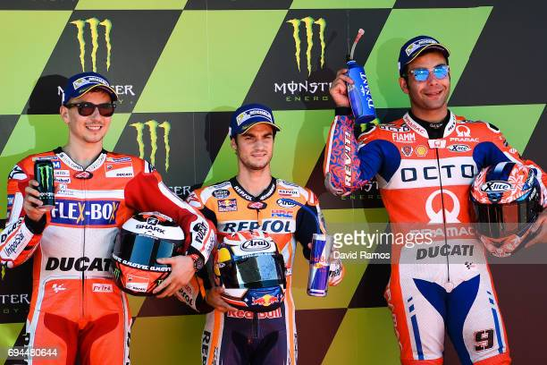 Dani Pedrosa of Spain and Repsol Honda Team poses next to Jorge Lorenzo of Spain and Ducati Team and second and Danilo Petrucci of Italy and OCTO...