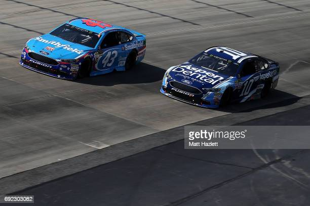Danica Patrick driver of the Aspen Dental Ford races Regan Smith driver of the Smithfield Ford during the Monster Energy NASCAR Cup Series AAA 400...