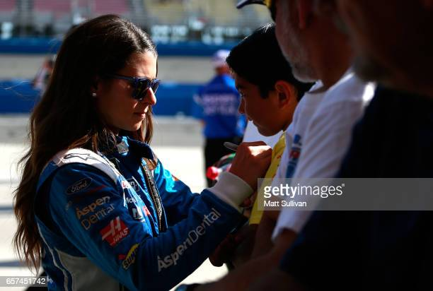 Danica Patrick driver of the Aspen Dental Ford signs autographs during qualifying for the Monster Energy NASCAR Cup Series Auto Club 400 at Auto Club...