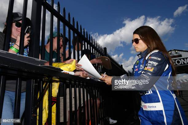 Danica Patrick driver of the Aspen Dental Ford signs autographs for fans prior to qualifying for the Monster Energy NASCAR Cup Series Axalta presents...