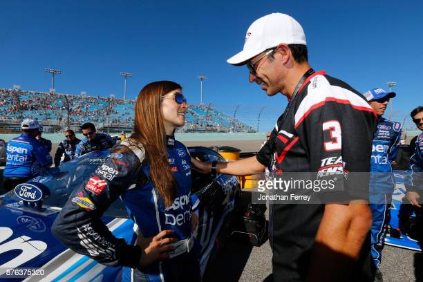 Danica Patrick driver of the Aspen Dental Ford speaks with race car driver Helio Castroneves on the grid prior to the Monster Energy NASCAR Cup...