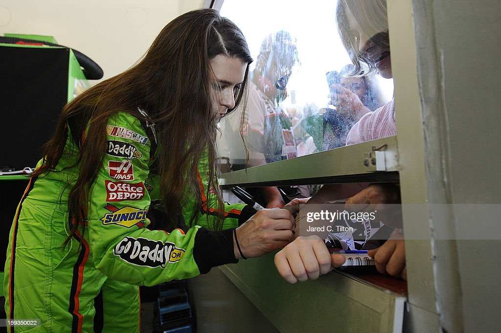 <a gi-track='captionPersonalityLinkClicked' href=/galleries/search?phrase=Danica+Patrick&family=editorial&specificpeople=183352 ng-click='$event.stopPropagation()'>Danica Patrick</a>, driver of the #10 Chevrolet, signs her autograph for fans in the garage area during NASCAR Sprint Cup Series Preseason Thunder testing at Daytona International Speedway on January 12, 2013 in Daytona Beach, Florida.