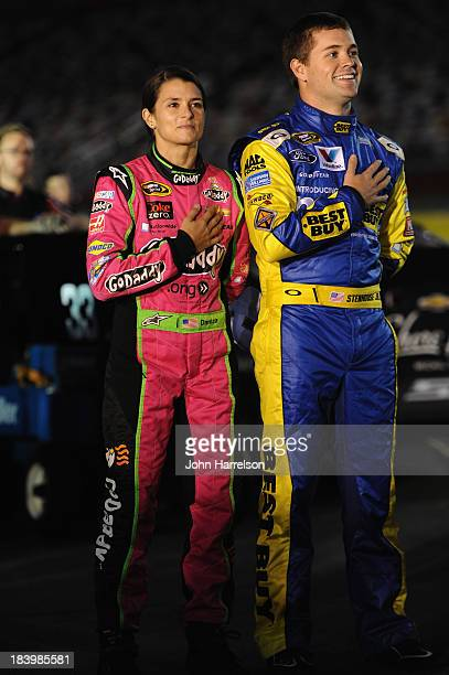 Danica Patrick driver of the GoDaddy Breast Cancer Awareness Chevrolet and Ricky Stenhouse Jr driver of the My Best Buy Ford stand on the grid during...