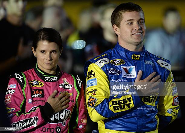 Danica Patrick driver of the GoDaddy Breast Cancer Awareness Chevrolet and Ricky Stenhouse Jr driver of the My Best Buy Ford stand on the grid prior...