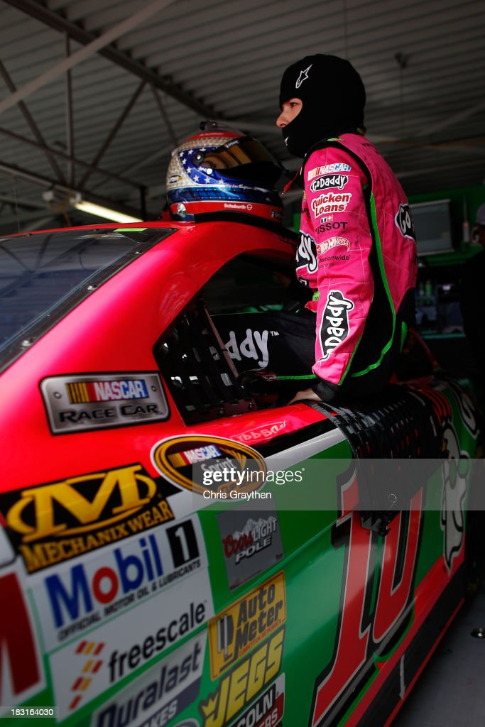 Danica Patrick, driver of the #10 GoDaddy Chevrolet, climbs into her car in the garage area during practice for the NASCAR Sprint Cup Series 13th Annual Hollywood Casino 400 at Kansas Speedway on October 5, 2013 in Kansas City, Kansas.