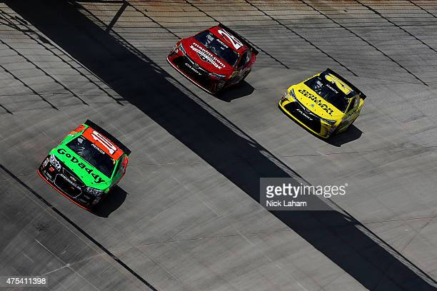 Danica Patrick driver of the GoDaddy Chevrolet leads Jeb Burton driver of the Maxim Fantasy Sports Toyota and Matt Kenseth driver of the Dollar...