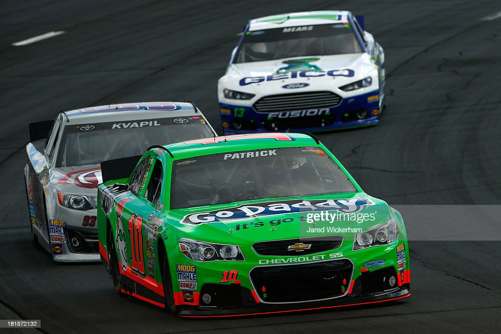 Danica Patrick, driver of the #10 GoDaddy Chevrolet, leads Travis Kvapil, driver of the #93 Burger King / Dr. Pepper Toyota, and Casey Mears, driver of the #13 GEICO Ford, during the NASCAR Sprint Cup Series Sylvania 300 at New Hampshire Motor Speedway on September 22, 2013 in Loudon, New Hampshire.